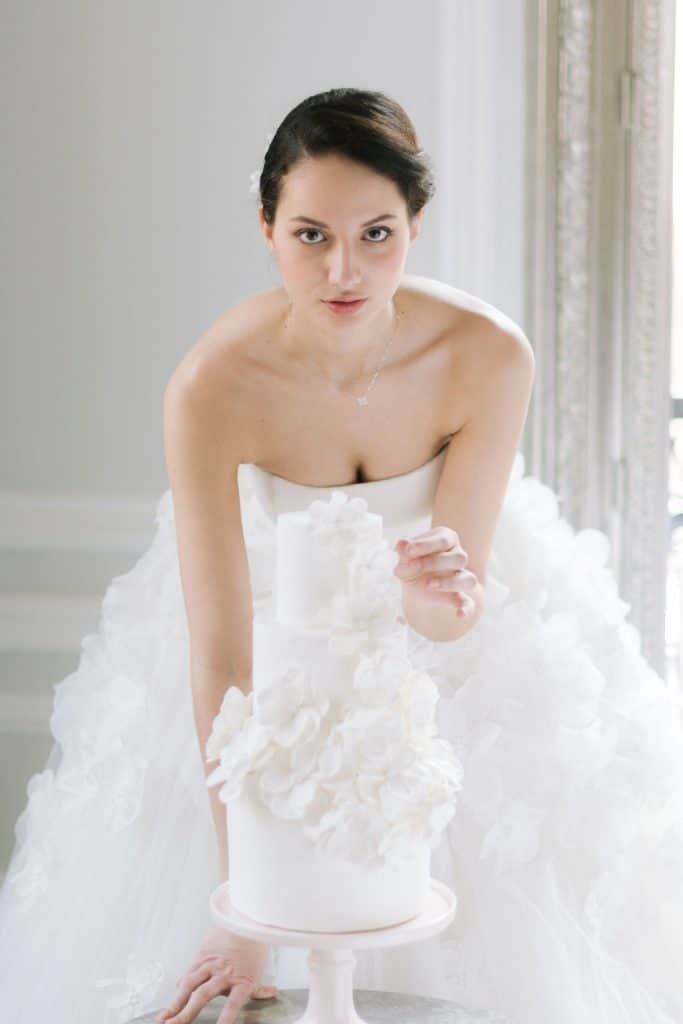 mariée en robe blanche qui regarde son wedding cake
