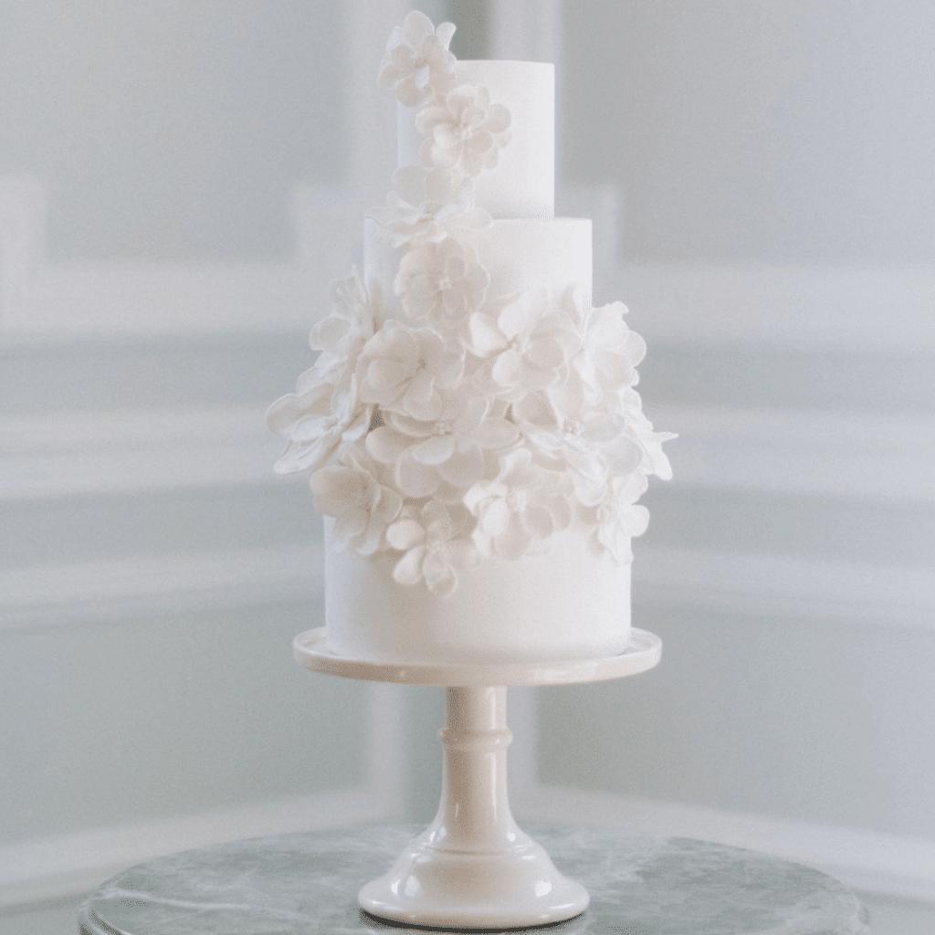 wedding cake blanc orné de pétales de fleursen pâte à sucre