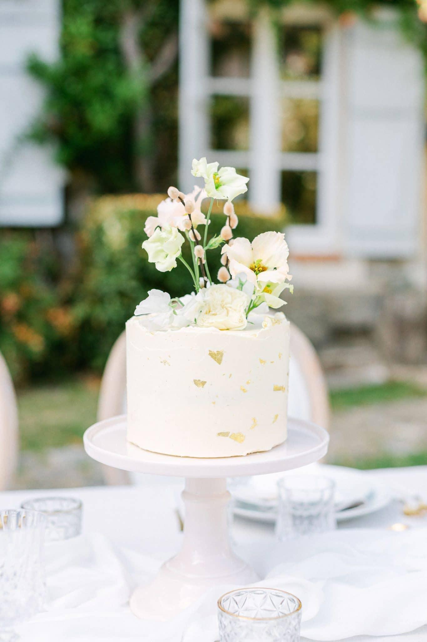 gâteau de célébration blanc avec des touches de feuille d'or et des fleurs fraîches en hauteur pour la décoration