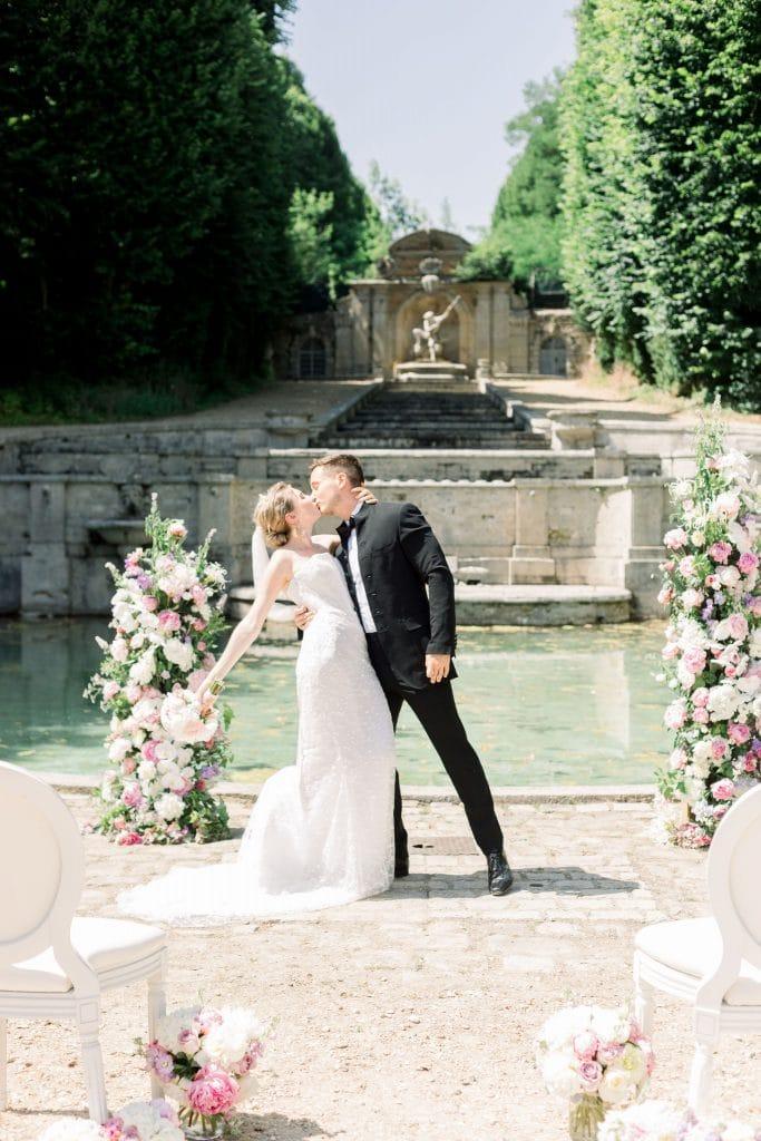 couple de mariés qui s'embrasse lors de leur cérémonie de mariage