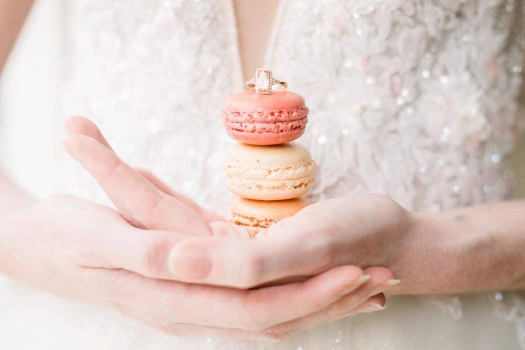 macarons présentés dans les mains d'une mariée